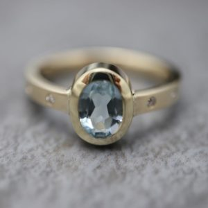 Bezel Set Oval Stone with Diamonds in Band