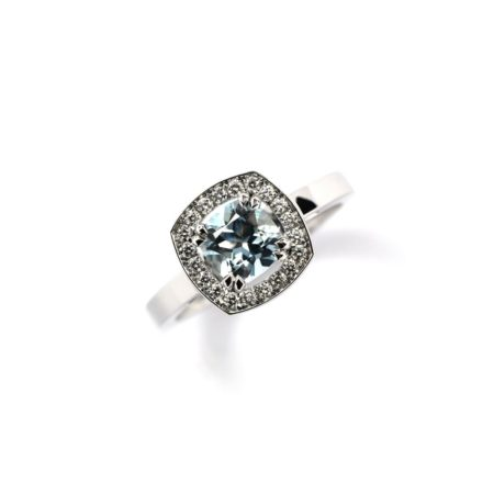 WHITE GOLD RING WITH AN AQUAMARINE CENTRE STONE SURROUNDED BY A HALO OF DIAMONDS IN A CUSHION SHAPED SETTING